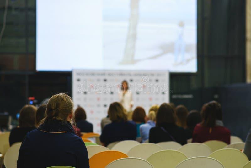 Opinião traseira os participantes do seminário, do treinamento ou da leitura em uma grande audiência com uma grande tela fotos de stock