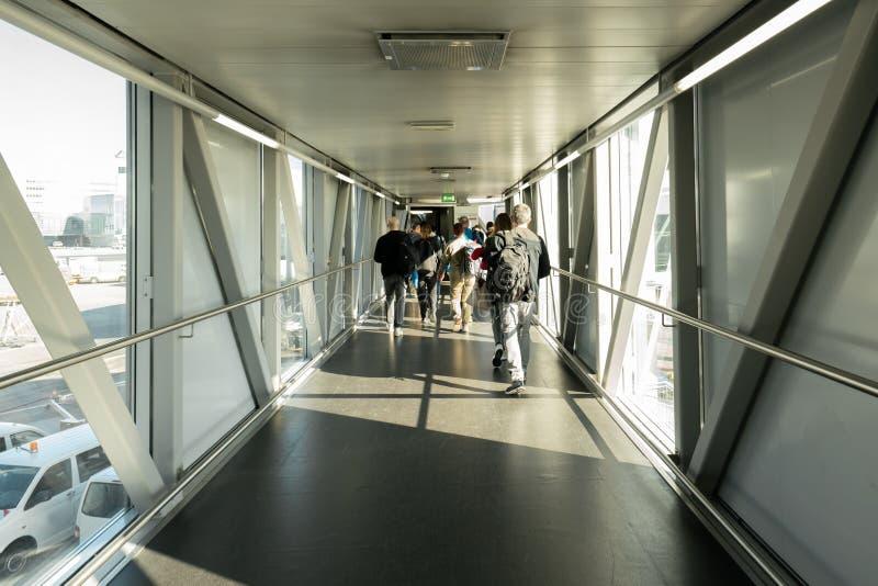 Opinião traseira os passageiros na ponte do aeroporto, ponte de uma linha aérea do jato onde os passageiros conectam com o plano  fotos de stock royalty free