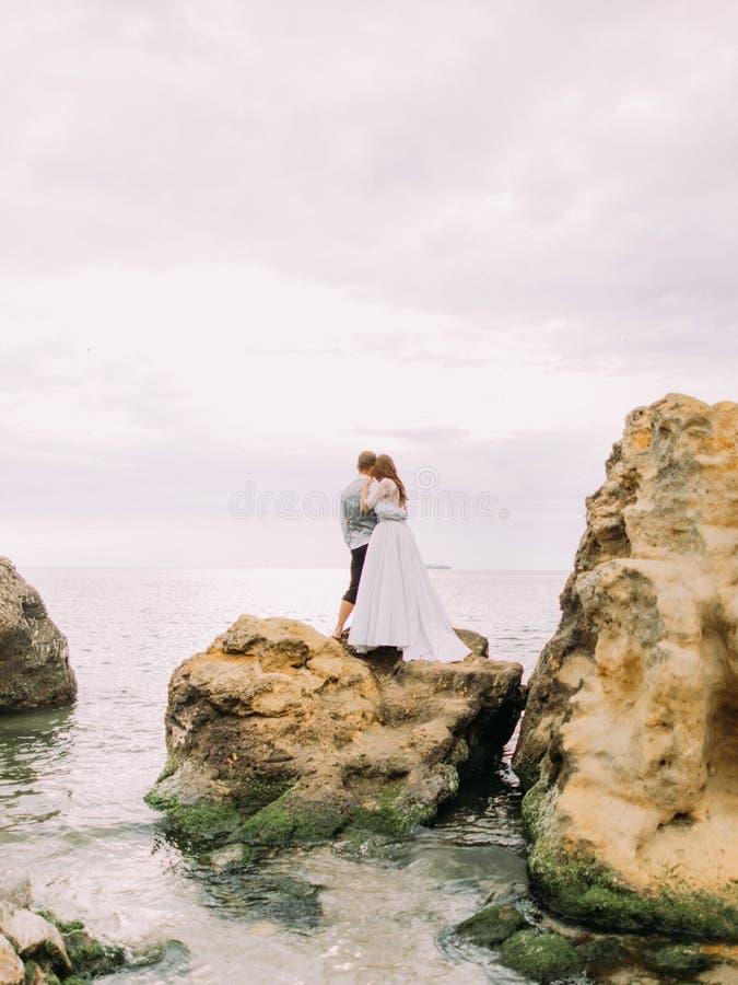 A opinião traseira os recém-casados que abraçam e que olham o por do sol ao estar no penhasco entre o mar fotografia de stock