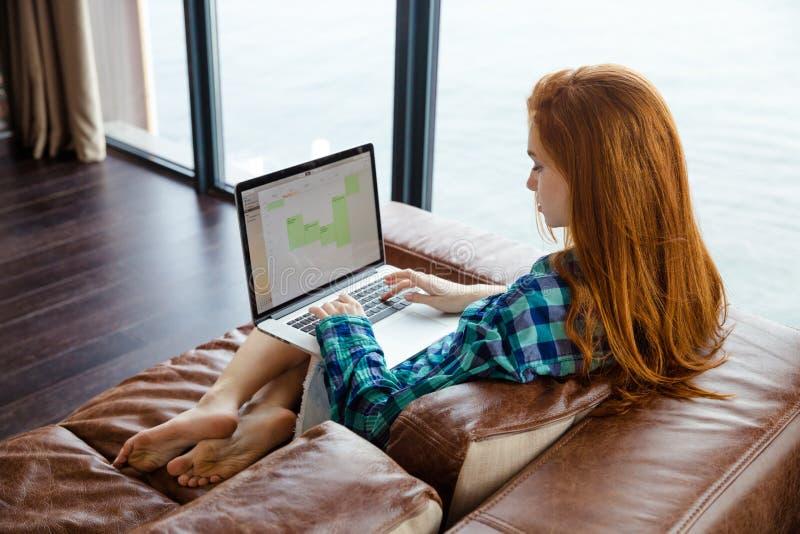 Opinião traseira a senhora que trabalha com o portátil no sofá foto de stock royalty free