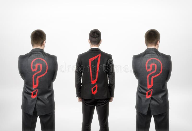 Opinião traseira três homens de negócios com ponto de interrogação e exclamação um no centro fotografia de stock