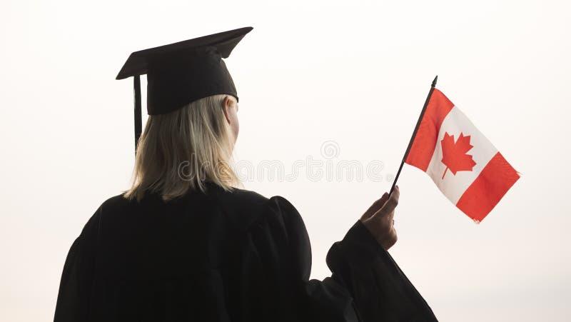 Opinião traseira um graduado com a bandeira de Canadá à disposição Estudo em Canad? imagens de stock