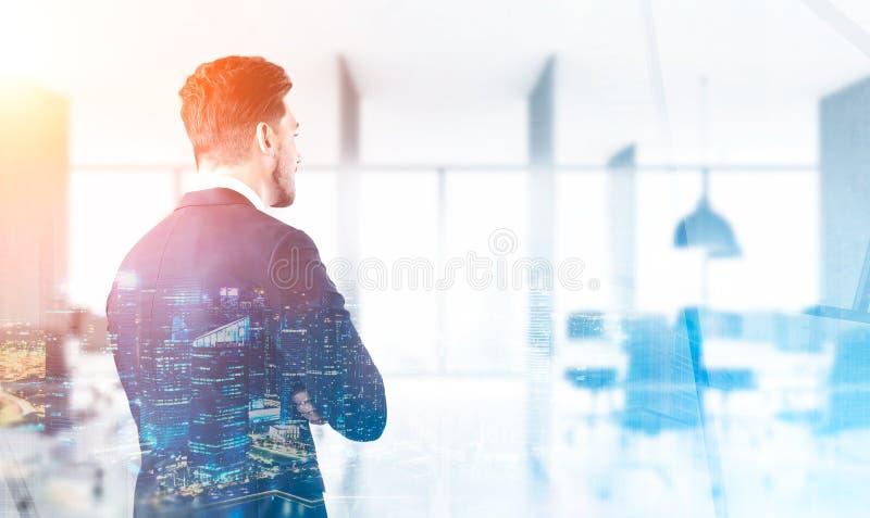 Opinião traseira um homem de negócios que olha a cidade de seu escritório, tom fotos de stock