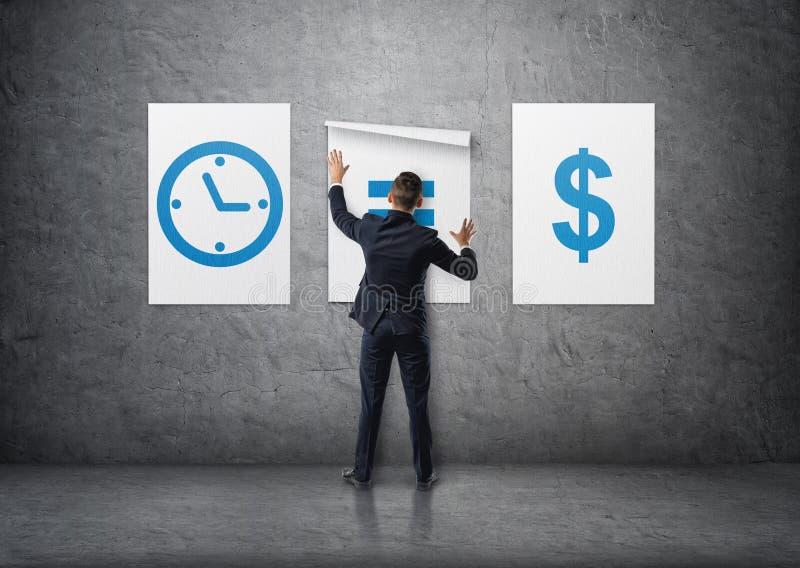 Opinião traseira um homem de negócios que une cartazes & x27; o tempo é o money& x27; no muro de cimento foto de stock
