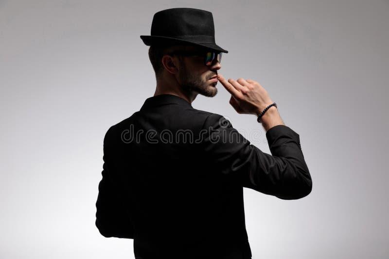 Opinião traseira um homem ocasional misterioso que gesticula o silêncio imagens de stock royalty free