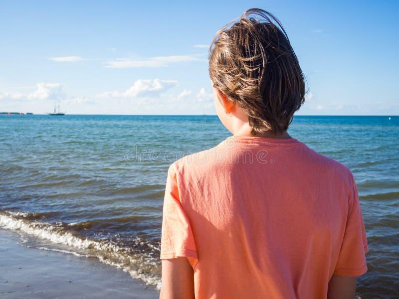 Opinião traseira um menino do adolescente na praia imagem de stock