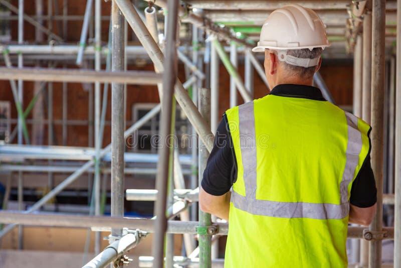Opinião traseira um trabalhador da construção no terreno de construção fotografia de stock