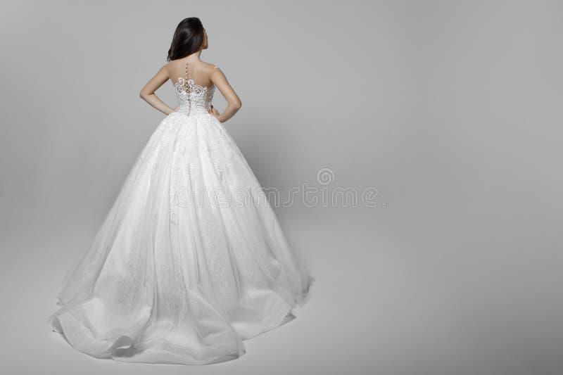 Opini?o traseira uma jovem mulher com cabelo longo no vestido de casamento branco, m?os em sua cintura, em um fundo branco fotos de stock royalty free