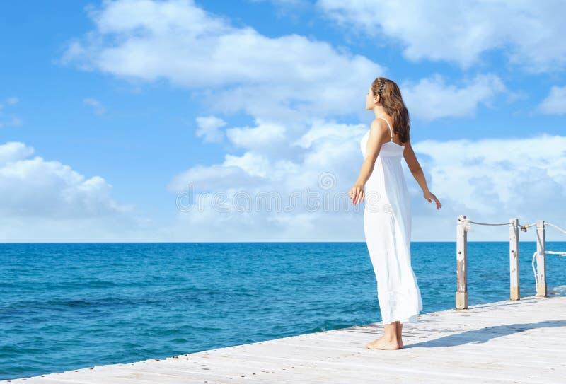 Opinião traseira uma jovem mulher que está em um cais Parte traseira do mar e do céu foto de stock