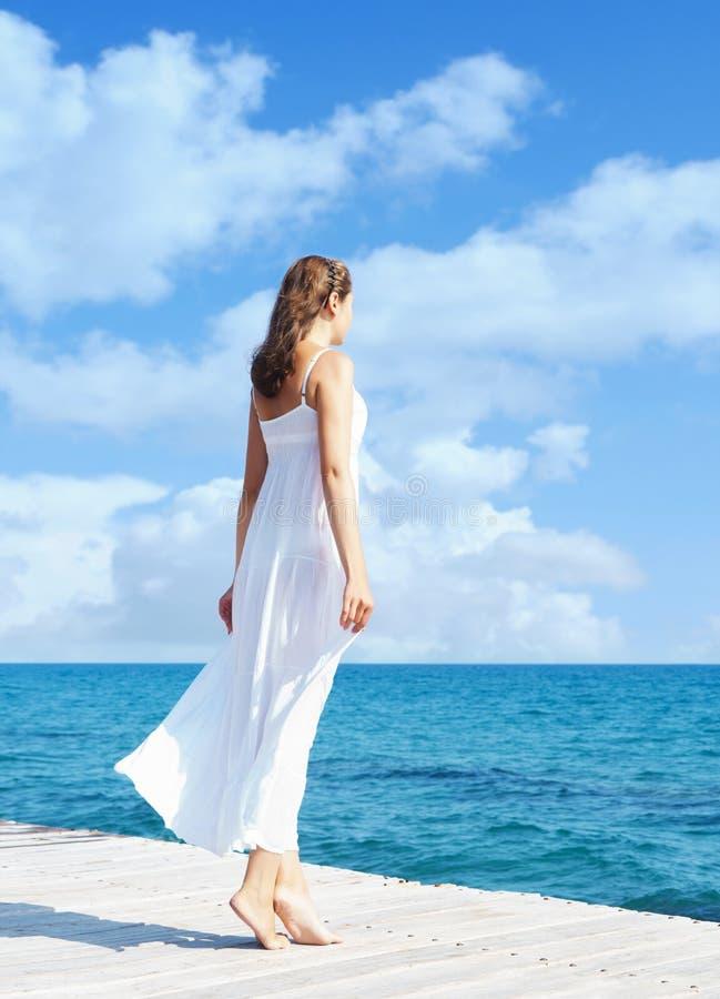 Opinião traseira uma jovem mulher que está em um cais Parte traseira do mar e do céu imagens de stock