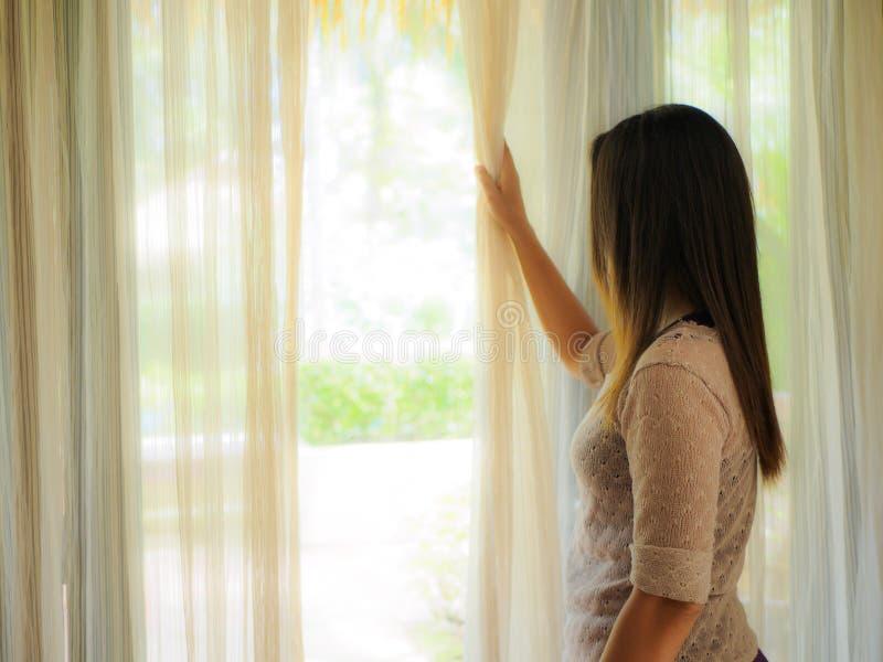 A opinião traseira uma jovem mulher que guarda as cortinas abre para olhar em casa fora de uma grande janela clara fotos de stock royalty free