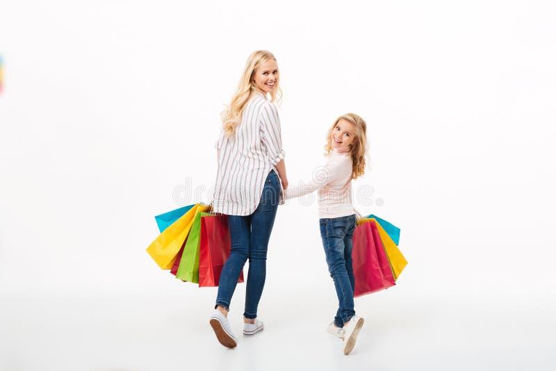 Opinião traseira uma mãe de sorriso e sua filha pequena imagem de stock royalty free