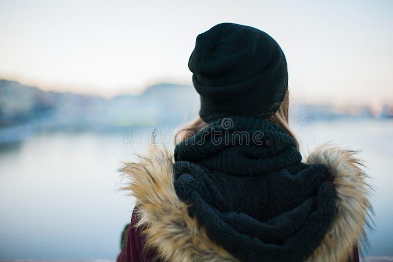Opinião traseira uma menina do moderno contra o backgroun borrado do inverno fotografia de stock royalty free