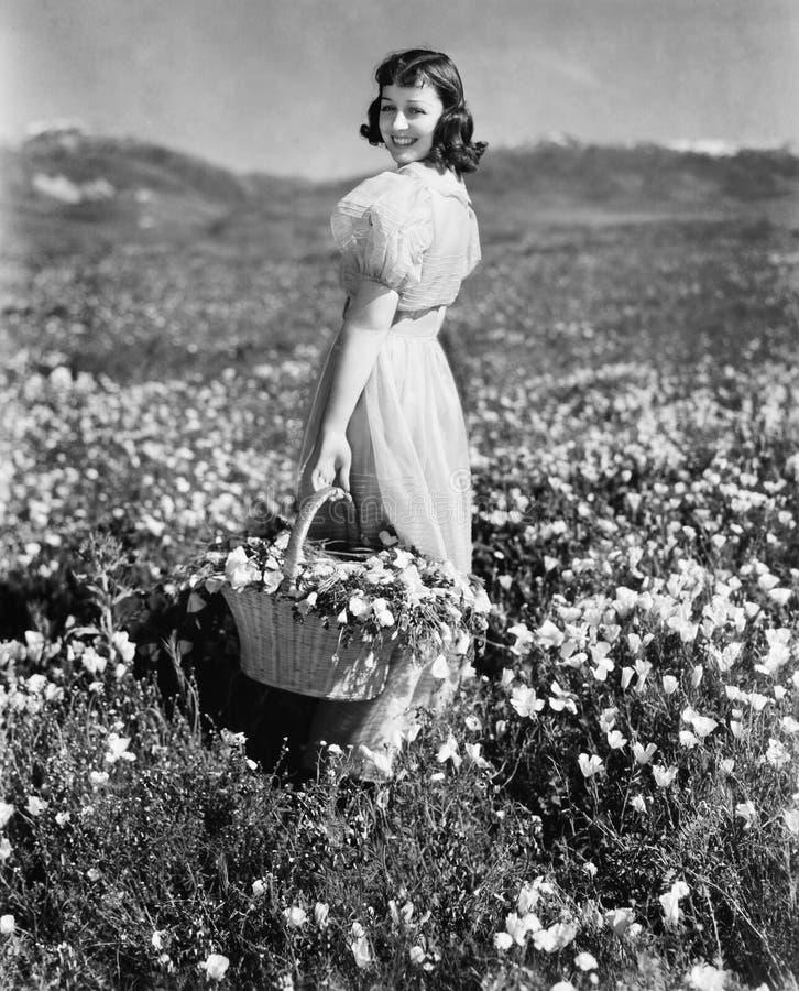 Opinião traseira uma menina que está em um prado que guarda uma cesta da flor e sorriso (todas as pessoas descritas não são umas  imagem de stock royalty free