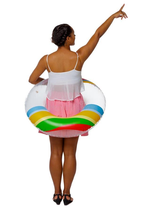 Opinião traseira uma mulher afro-americana com um círculo inflável que aponte a mão acima fotos de stock royalty free