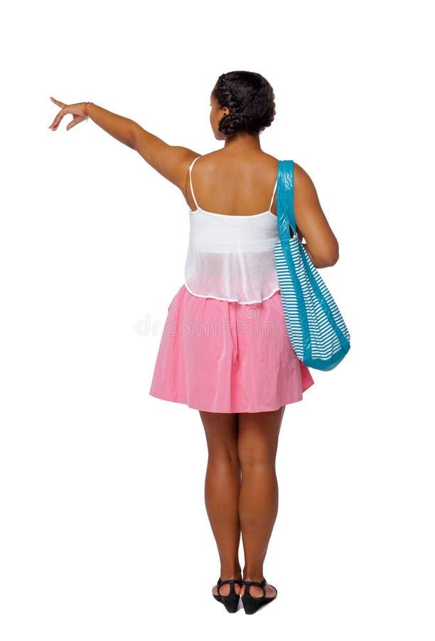 Opinião traseira uma mulher afro-americana com um círculo inflável que aponte a mão acima fotografia de stock