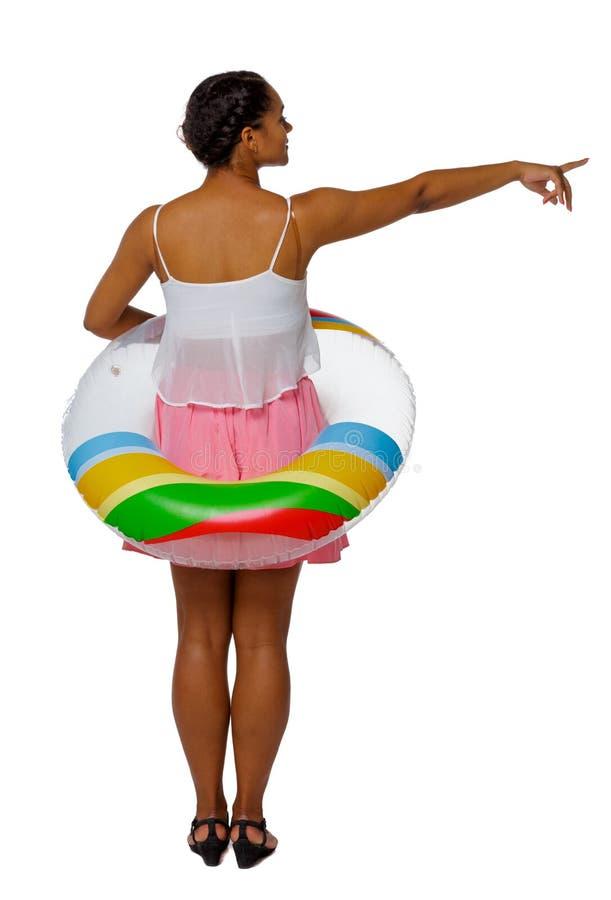Opinião traseira uma mulher afro-americana com um círculo inflável que aponte a mão acima foto de stock