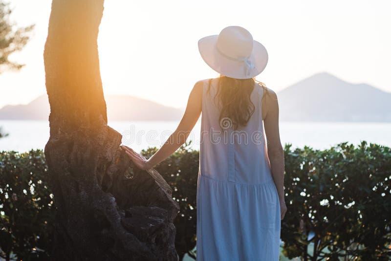 Opinião traseira uma mulher bonita nova que guarda seu chapéu de palha na praia e que olha ao horizonte de mar fotografia de stock