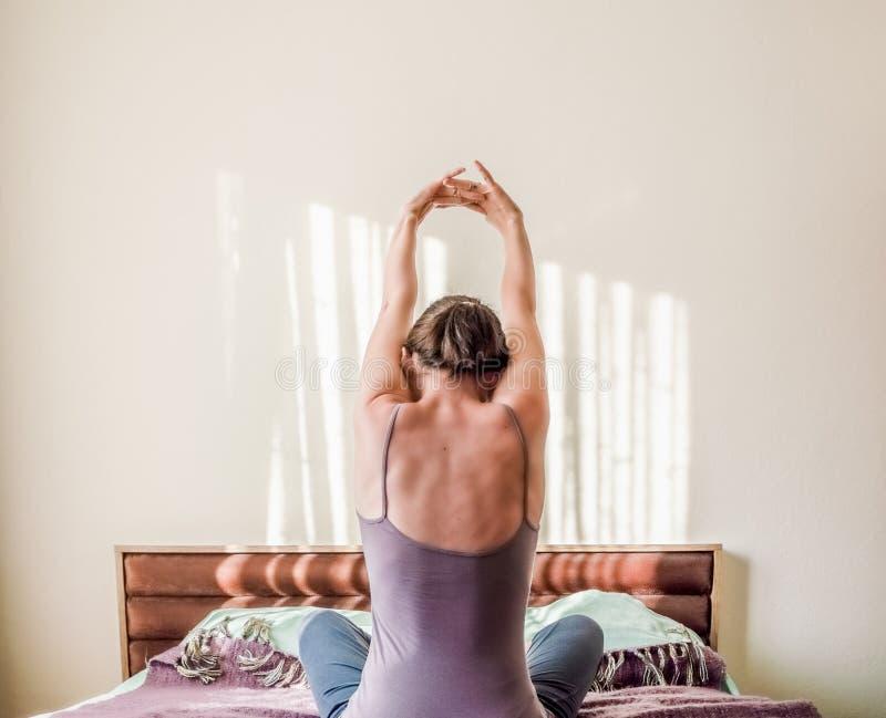 Opinião traseira uma mulher caucasiano que acorda na cama e que estica seus braços com espaço da cópia imagens de stock royalty free