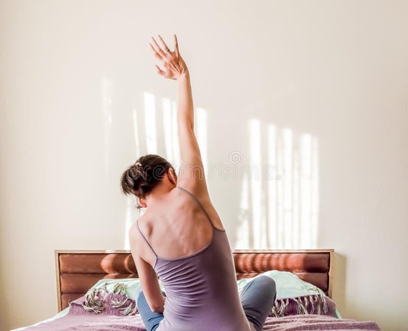 Opinião traseira uma mulher caucasiano que acorda na cama e que estica seus braços com espaço da cópia imagens de stock