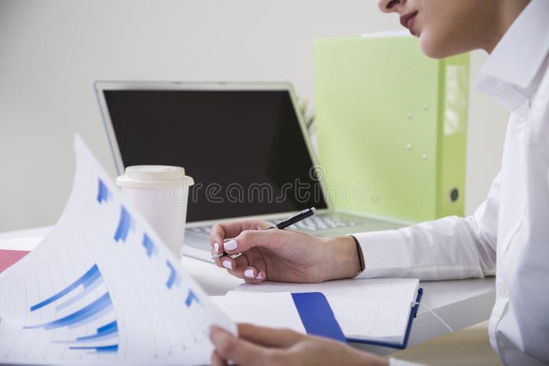 Opinião traseira uma mulher de negócios de cabelo marrom pensativa em uma blusa branca que senta-se em sua tabela em um escritóri imagem de stock royalty free