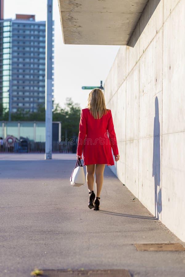 Opinião traseira uma mulher elegante que veste o revestimento vermelho, saia e guardando uma bolsa branca ao andar na rua em um d foto de stock