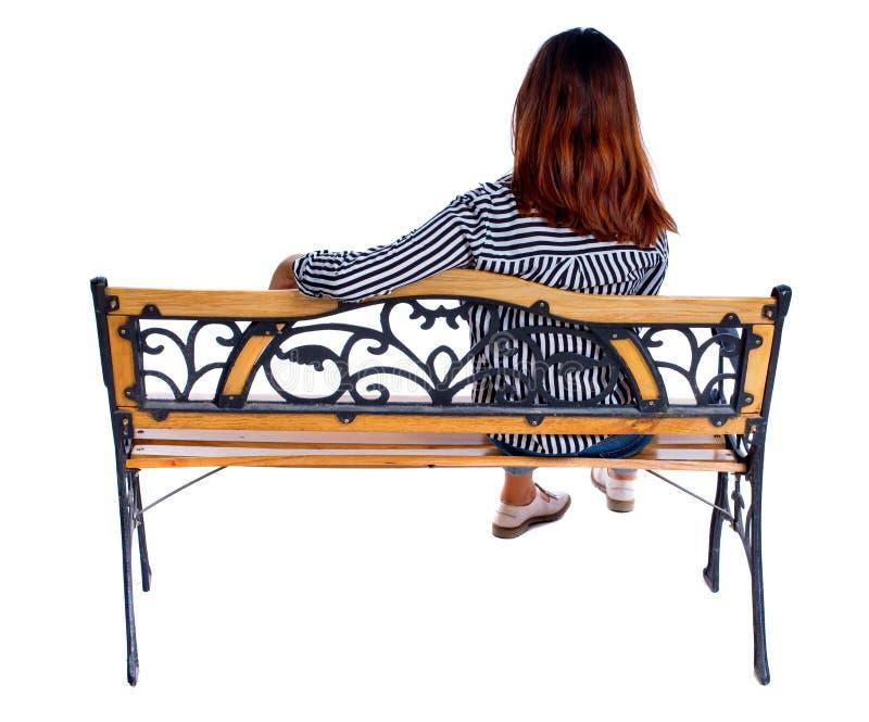 Opinião traseira uma mulher que senta-se no banco imagens de stock royalty free