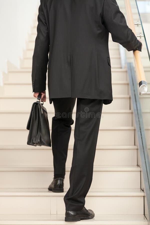 Opinião traseira uma pessoa do negócio que ascensão as escadas fotos de stock