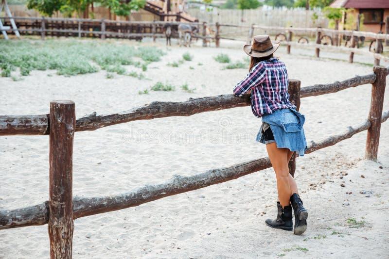 Opinião traseira a vaqueira da mulher que está a cerca próxima no rancho fotos de stock