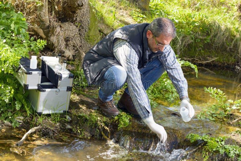 A opinião um biólogo toma uma amostra em um rio fotografia de stock