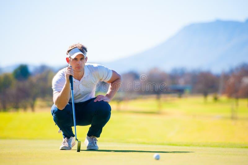Opinião um jogador de golfe que planeia seu tiro ao pino foto de stock royalty free