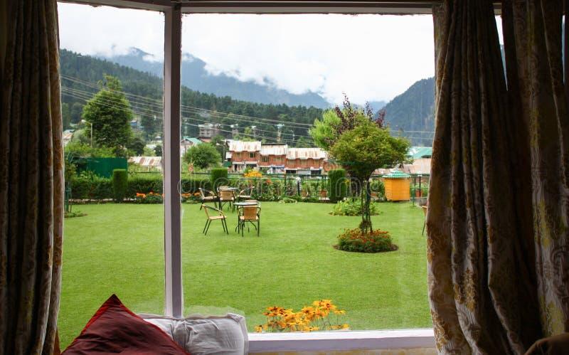 Opinião verde do jardim do parque da janela em um bom dia fotografia de stock royalty free