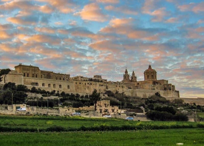 Opinión épica de la puesta del sol de la catedral de San Pablo y del horizonte de la ciudad fortificada emparedada medieval Mdina fotografía de archivo
