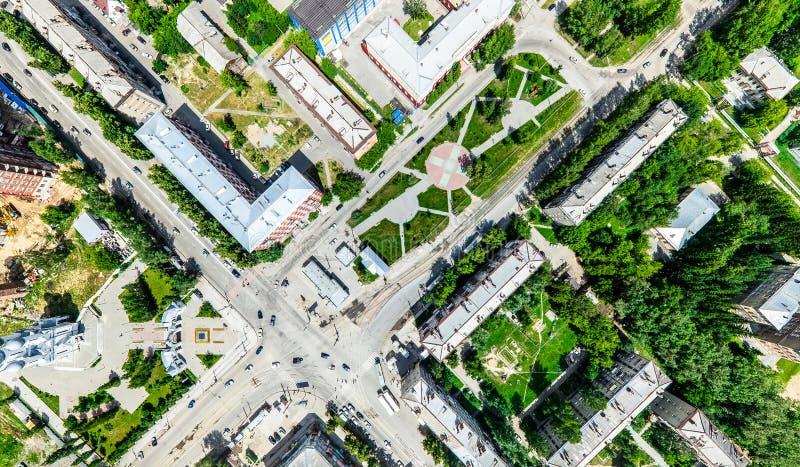 Opinión aérea de la ciudad con los cruces y caminos, casas, edificios, parques y estacionamientos Imagen panorámica del verano so imagen de archivo libre de regalías
