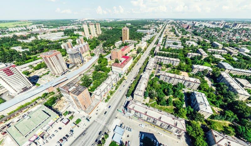 Opinión aérea de la ciudad con los cruces y caminos, casas, edificios, parques y estacionamientos Imagen panorámica del verano so foto de archivo
