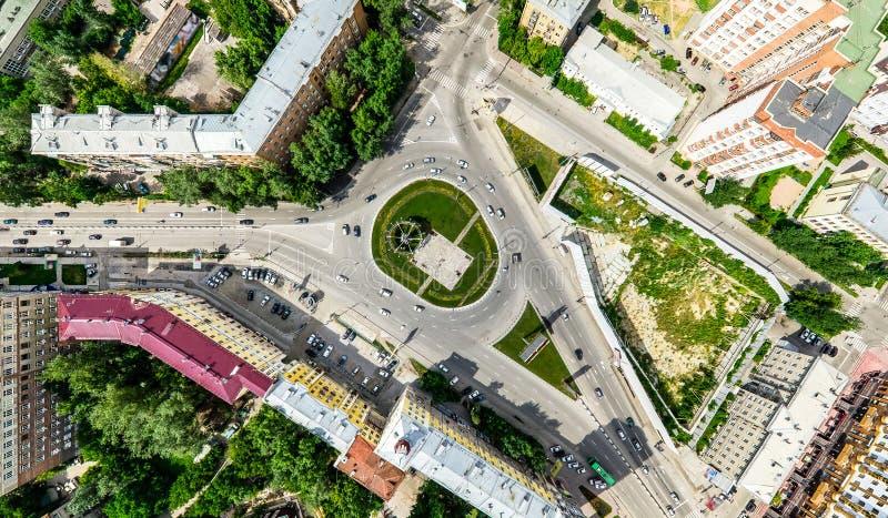 Opinión aérea de la ciudad con los cruces y caminos, casas, edificios, parques y estacionamientos Imagen panorámica del verano so imágenes de archivo libres de regalías