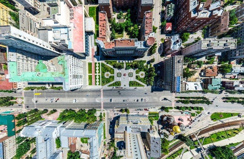 Opinión aérea de la ciudad con los cruces y caminos, casas, edificios, parques y estacionamientos Imagen panorámica del verano so imagen de archivo
