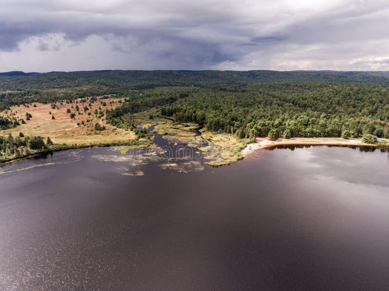 Opinión aérea de la naturaleza del contryside de Ontario Canadá que mira abajo desde arriba del río que fluye dentro del lago foto de archivo