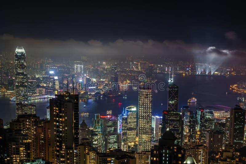 Opinión aérea de la noche del pico de Victoria a la bahía y al illumina de Kowloon imagenes de archivo