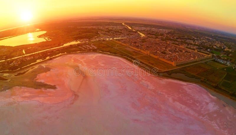 Opinión aérea de la puesta del sol que sorprende de la ciudad antigua Aigues-Mortes, del lago de sal rosado grande y de los panta fotos de archivo libres de regalías