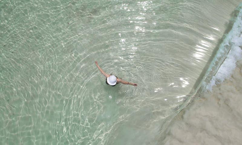 Opinión aérea del abejón aéreo la muchacha hermosa que se divierte en la playa tropical soleada Seychelles foto de archivo