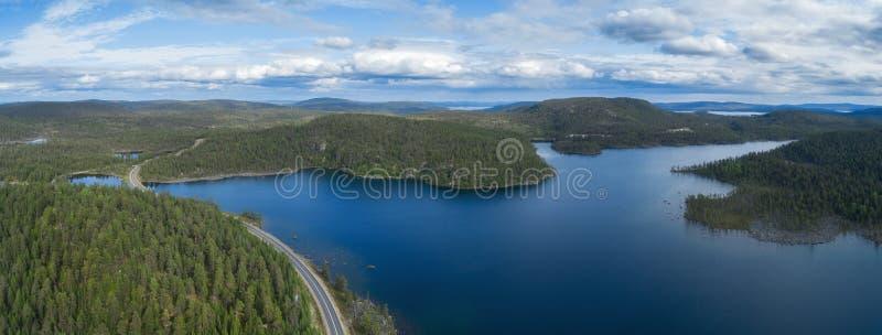 Opinión aérea del abejón de un camino a través del bosque y de colinas en Laponia en un día nublado Lago hermoso con agua azul fotografía de archivo