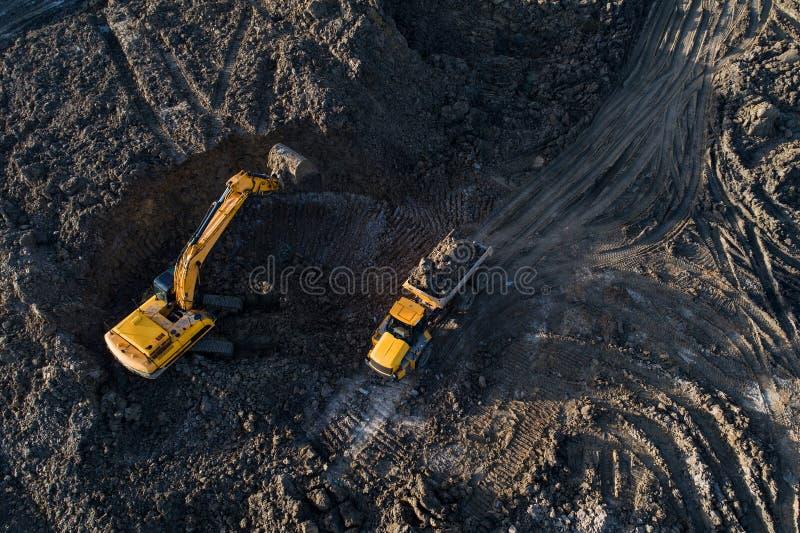 Opinión aérea del abejón del excavador que carga el camión de volquete imagen de archivo libre de regalías