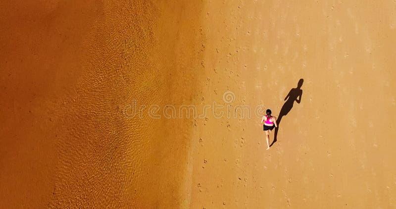 Opinión aérea del abejón la mujer juguetona sana que corre en la playa fotografía de archivo