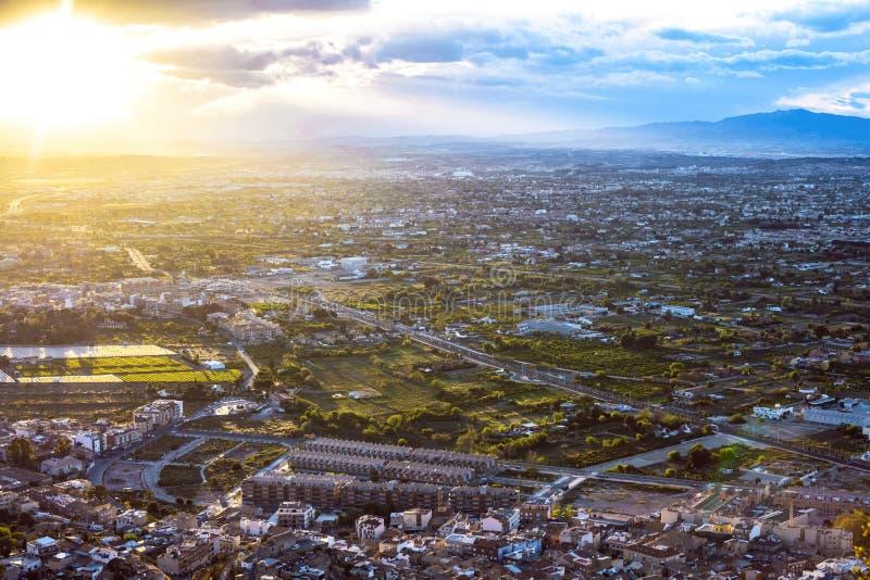 Opinión aérea del paisaje urbano de la ciudad de Murcia, de las montañas durante una puesta del sol hermosa fotos de archivo