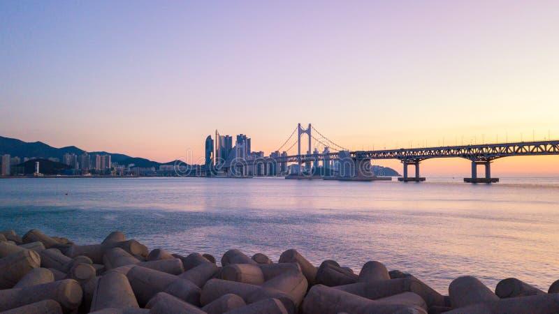 Opinión aérea del puente y de Haeundae de Gwangan en la salida del sol, Busán, del sur imagen de archivo