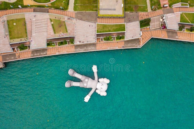 Opinión aérea el compañero de KAWS, escultura gigante que flota en el agua Figura en Victoria Harbour, Hong Kong La República de  imágenes de archivo libres de regalías