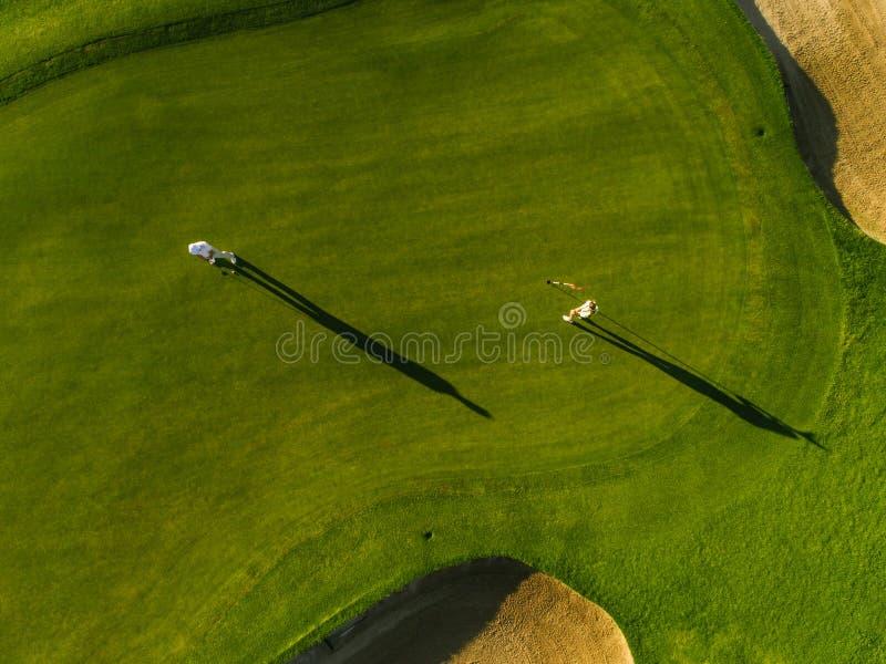Opinión aérea los golfistas que juegan en curso fotos de archivo