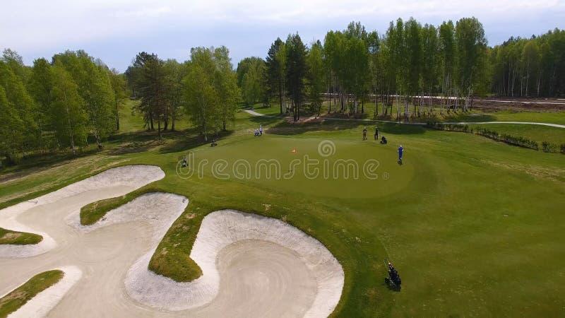 Opinión aérea los golfistas que juegan en putting green Jugadores profesionales en un campo de golf verde fotografía de archivo libre de regalías