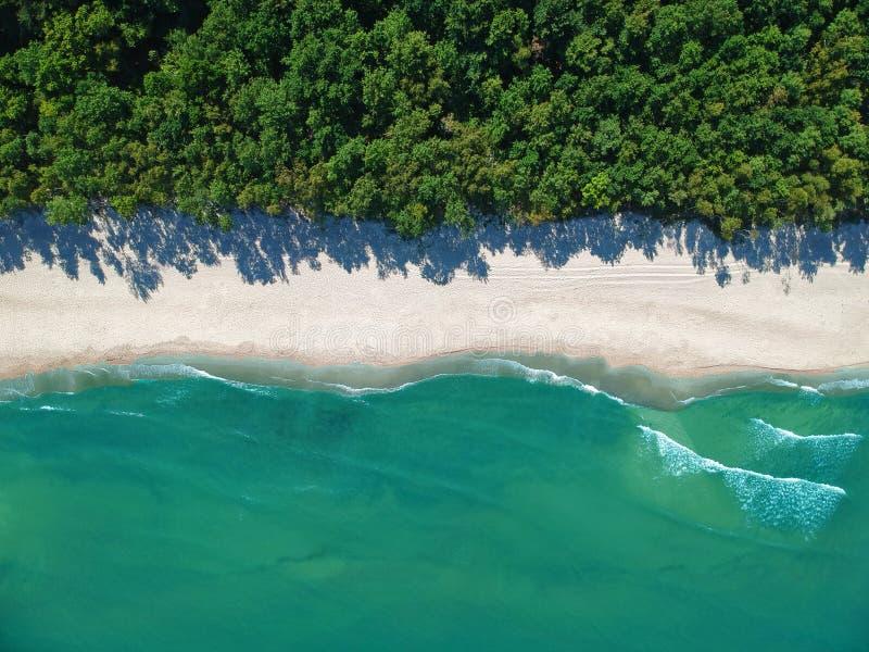 Opinión aérea sobre el agua del océano de la turquesa con la playa y el bosque vacíos limpios de la arena imagenes de archivo